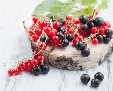 Freshly collected ripe redcurrants and blackcurrants with leaves on wooden background