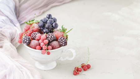 Assortment of frozen berries in white cup on the stone concrete background with copy space