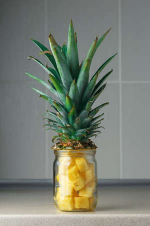 Fresh juicy pineapple pieces in a glass jar on the kitchen table against grey rile background