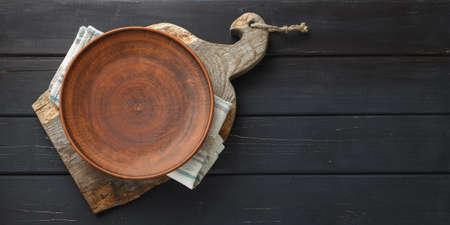 Empty clay dish on rustic cutting board over black wooden background Standard-Bild