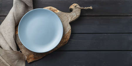 Empty blue dish on rustic cutting board over black wooden background