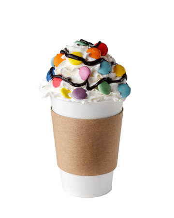 Coffee drink covered with whipped cream, chocolate syrup and colorful candies in paper cup to go isolated on white background