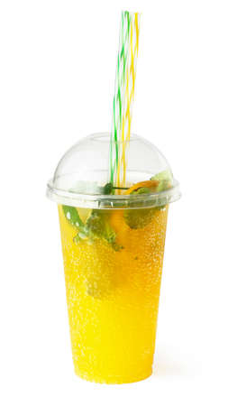 Orange lemonade in plastic glass, cooling fruit drink with sparkling water and mint isolated on white background