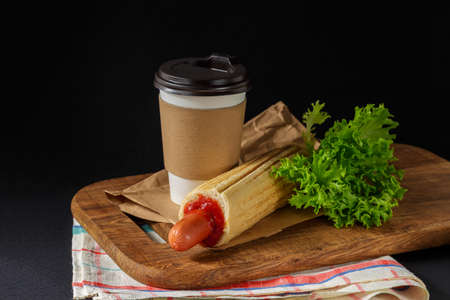 French Hot Dog and coffee to go on wooden cutting board over black background. Fast food meal menu