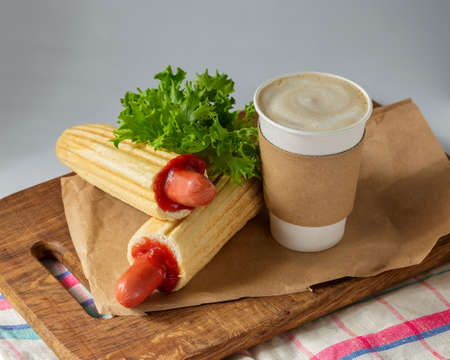 French Hot Dog and coffee to go on wooden cutting board over grey background. Fast food meal menu