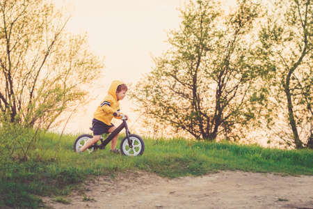 Little boy rides a balance bike in the countryside at sunset. Run bicycle without pedals