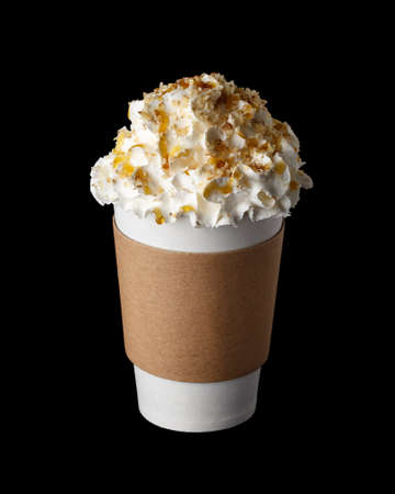 Coffee drink covered with whipped cream, caramel syrup and chopped peanuts in paper cup to go isolated on black background Standard-Bild