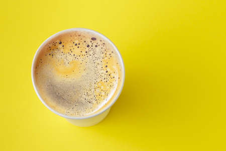 Top view of take-out hot drink in opened thermo cup on vibrant yellow background. Cafe crema foam on the americano coffee 版權商用圖片