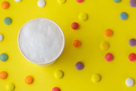 Top view of take-out coffee Latte in opened thermo cup on vibrant yellow background, colorful candies scattered around
