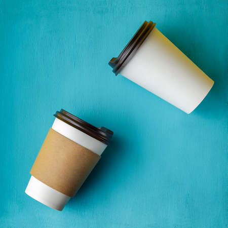 Take away coffee drink in disposable paper cup over turquoise wooden background Standard-Bild