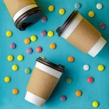 Take away coffee drink in disposable paper cup and colorful candies scattered over turquoise wooden background