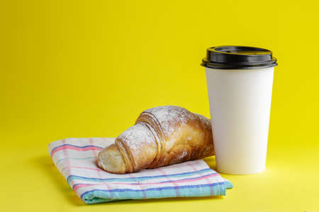 Take away coffee drink with croissant on yellow background