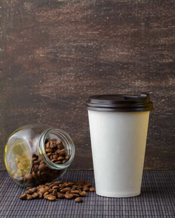 Take away coffee drink in disposable paper cup over rustic wooden background Standard-Bild