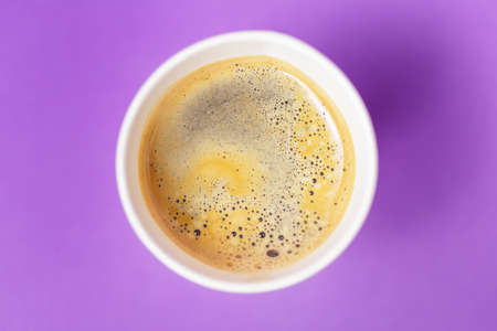 Top view of take-out hot drink in opened thermo cup on vibrant purple background. Cafe crema foam on the americano coffee Standard-Bild