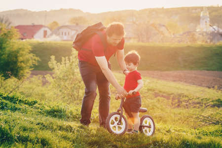 Father teaches his son to ride a balance bike in the countryside at sunset. Run bicycle without pedals Standard-Bild