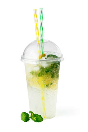 Cooling lemonade drink in plastic glass with lemon slices, mint and sparkling water isolated on white background