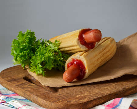 Two French Hot Dogs with lettuce on wooden cutting board over grey background. Fast food meal menu
