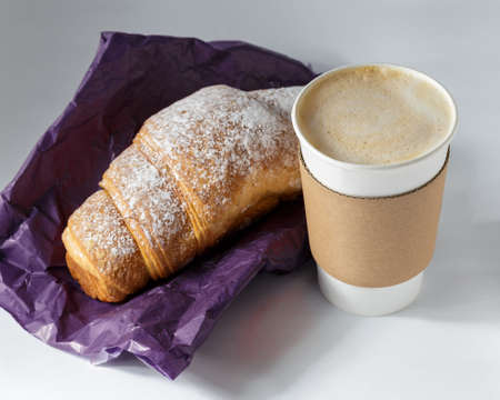 Take away coffee drink with croissant on grey background