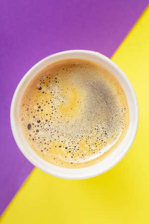 Top view of take-out hot drink in opened thermo cup on vibrant purple and yellow background. Cafe crema foam on the americano coffee