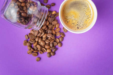 Top view of take-out hot drink in opened thermo cup and coffee beans scattered from glass jar on vibrant purple background. Cafe crema foam on the americano coffee
