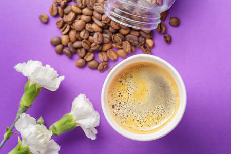 Top view of take-out hot drink in opened thermo cup, coffee beans scattered from glass jar and white flowers on vibrant purple background. Cafe crema foam on the americano coffee
