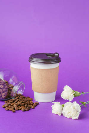 Take-out hot drink in closed paper cup, coffee beans scattered from glass jar and white flowers on vibrant purple background