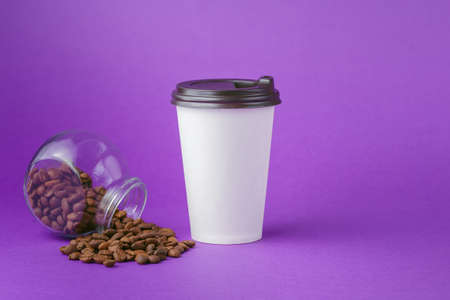 Take-out hot drink in closed paper cup, coffee beans scattered from glass jar on vibrant purple background