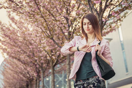 Unsatisfied young woman waiting for the meeting or date and checks time on wrist watches. Beautiful lady standing among blooming sakura trees on the street