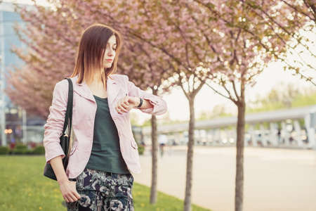 Young woman waiting for the meeting or date and checks time on wrist watches. Beautiful lady standing among blooming sakura trees on the street Standard-Bild