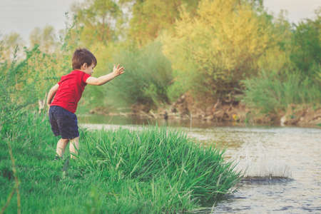 Little boy throws a rock ino the river. Summer vacation activities