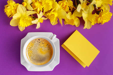 Cup of coffee, empty message card and yellow narcissus flowers on vibrant purple background, spring holiday greetings, top view