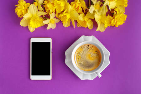 Coffee cup with narcissus flowers and smart phone on colorful purple background, flat lay Standard-Bild