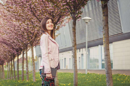 Woman portrait over pink blooming trees in the city street. Beautiful young lady holding her paper notebook near modern building