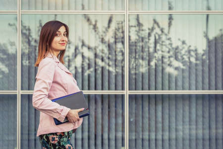 Beautiful young woman portrait holding her paper notebook and laptop near modern building Standard-Bild