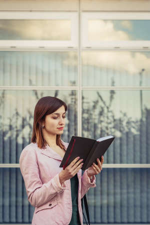 Beautiful young lady checking her day schedule in paper notebook near modern office building