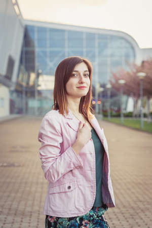 Portrait of young woman standing on the street near contemporary building
