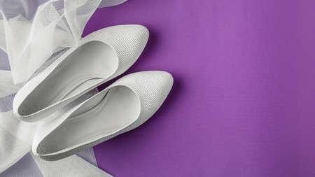 White wedding shoes with veil on purple background Standard-Bild