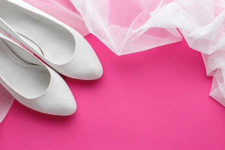 White wedding shoes with veil on pink background
