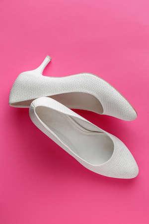 Simple white wedding shoes on pink background Standard-Bild