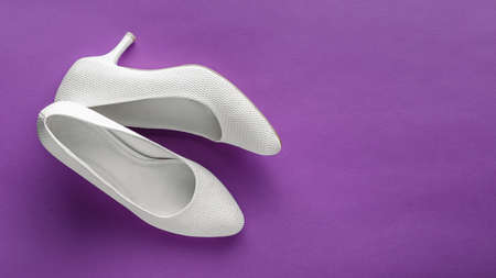 Simple white wedding shoes on purple background