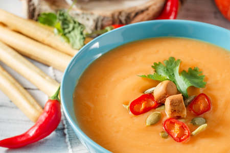 Pumpkin soup with chili pepper, pumpkin seeds, croutons and parsley in blue bowl on white wooden background