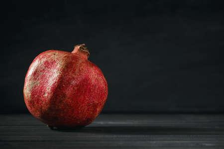 Pomegranate fruit on black wooden background. Healthy food concept Standard-Bild