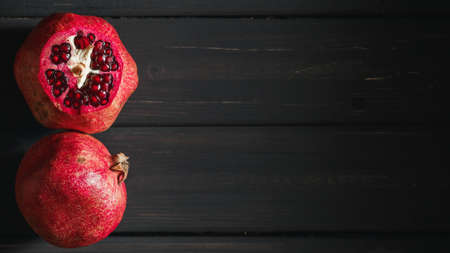 Pomegranate fruit on black wooden background. Healthy food concept Stock Photo