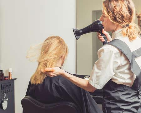 Beautician blow drying woman's hair at beauty salon