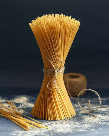 Bunch of uncooked Italian pasta spaghetti on a blue background