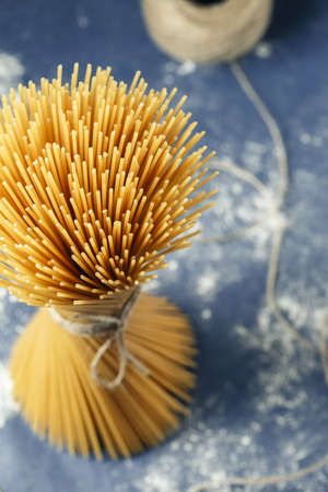 Bunch of uncooked Italian pasta spaghetti on a purple background. Macro shot, selective focus Imagens