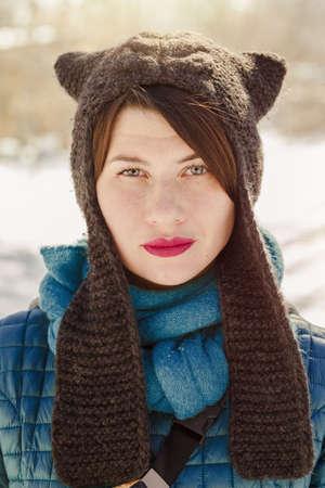 Portrait of stylish woman wearing funny winter knitted like cat ears hat