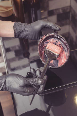 Stylist preparing a hair dye in a container, hairdresser salon concept Archivio Fotografico