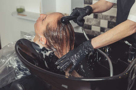 Hair wash procedure in a beauty salon. A hair dresser is washing her clients head in professional sink
