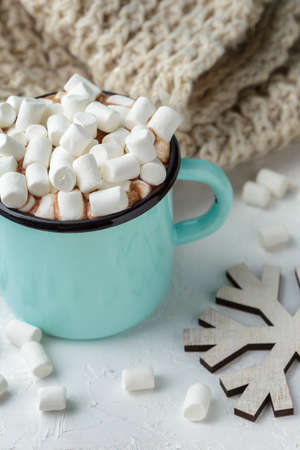 Blue metal mug of cocoa or hot chocolate with marshmallows on the table with winter decor, branch of corton flower, knitted blanket and wooden Christmas ornaments